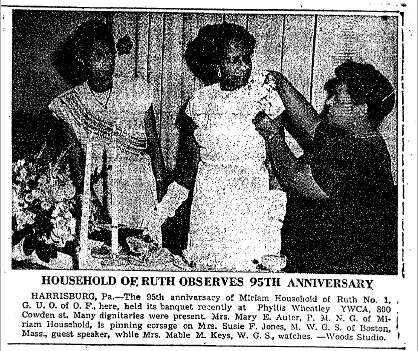 """A newspaper clipping with a black and white photo of three black women. The one on the right is pinning a corsage on the one in the middle, while the woman on the left watches. The caption reads """"household of Ruth observes ninety-fifth anniversary. Harrisburg, Pennsylvania. The ninety-fifth anniversary of Miriam Household of Ruth Number One, Great United Order of Odd Fellows here, held its banquet recently at Phyllis Wheatley YWCA, 800 Cowden Street. Many dignitaries were present. Mrs. Mary E. Auter, P.M.N.G. of Miriam Household, is pinning corsage on Mrs. Susie F. Jones, M.W.G.S. of Boston, Massachusetts, guest speaker, while Mrs. Mable. M. Keys, W.G.S., watches."""""""